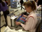Action on price fixing LIB ENGLAND London INT Shoppers at tills in crowded Asda supermarket CBV Cashier sitting at till scanning goods CS Till CMS...