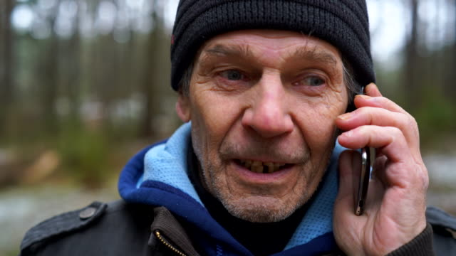 Active 70-years-old senior man talking via cellphone whem he walking in the winter forest