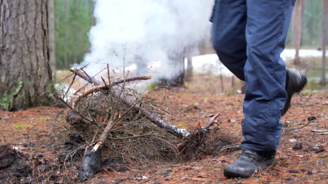 Active 70-years-old senior traveling man make fire in the winter forest.