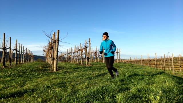 Active Adult Woman Running Thru Vineyards