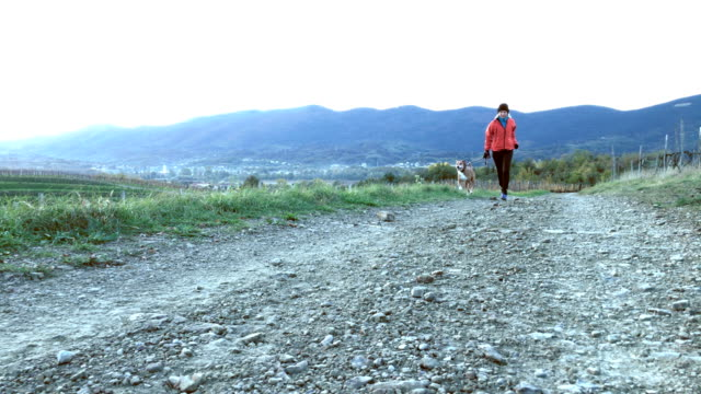 Active Adult Woman Running with her Dog in the Morning