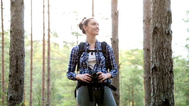 Active healthy Caucasian woman with a backpack taking pictures with an vintage film camera on a forest