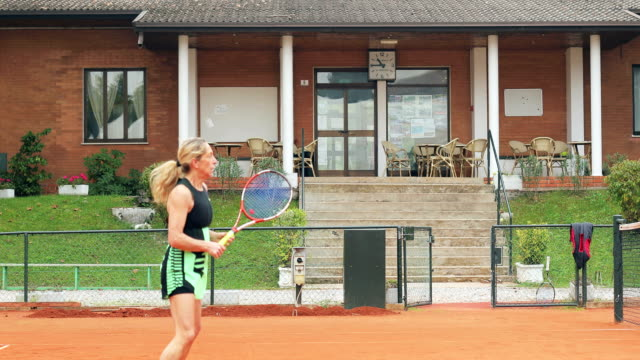 Active Mature Woman Playing Tennis on Private Tennis Court
