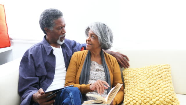 Active Senior African American Couple Reading Together on the Sofa