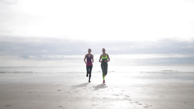Active senior woman running with daughter on beach