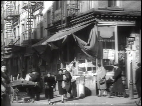 1939 HA Activities at Lower East side street corner with pedestrians walking and buying from a street vendor / New York, New York, United States