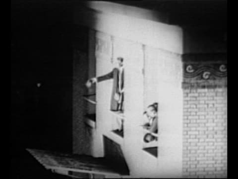 Activity on airfield with plane at left / night US Ambassador to France Myron T Herrick waves hat out window of airport building / crowd waves /...
