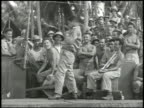 Actor comedian Joe E Brown on stage performing baseball act large crowds of United States Army soldiers watching laughing WWII Pacific Front...