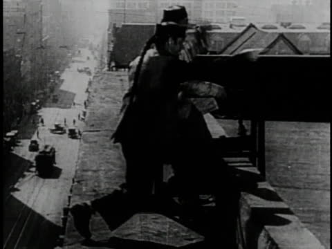 1920 B/W Actor fleeing from police and jumping over street to another rooftop in the silent film 'The Yellow Fear'