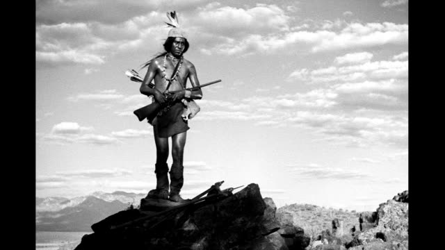 Actor playing Indian warrior standing on cliff smothering signal fire Native American Warrior on January 01 1940 in Arizona