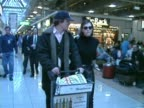 Actors High Grant and Liz Hurley walk through Heathrow before boarding flight Grant pushes airport trolley
