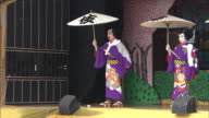 Actors in heavy makeup perform on an outdoor kabuki stage.