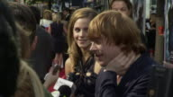 Actors Rupert Grint FG Emma Watson BG on crowded red carpet outside Ziegfeld Theater talking to press