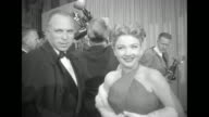 Actress Anne Baxter and director King Vidor stand in the lobby of the Pantages Theatre from which part of the Academy Awards are being televised for...