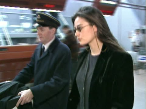 Actress Demi Moore flies out through Heathrow Airport A liveried assistant pushes her case and coat in trolley alongside her as she walks through...
