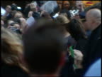 Actress Emma Watson on street w/ group security signing autographs for fans behind barricades