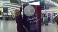 Actress Joanna Lumley poses with a plaque bearing her name at Heathrow Airport to mark it's 70th anniversary Various plaques commemorating...