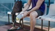 Adaptive athlete putting on running prosthetic leg