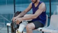 Adaptive runner putting on prosthetic limb