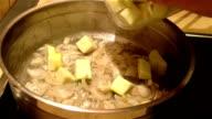 Adding a fresh zucchini to a frying onion