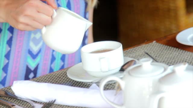 Adding cream to tea