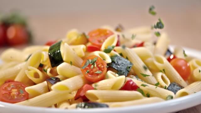 SLO MO peterselie toe te voegen aan een pasta met verse groenten