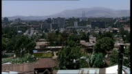 Addis Ababa cityscape / People sat outside Coptic Christian church More High angle shots of Cityscape / More of Corrugated iron roofs in foreground...