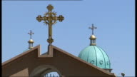 Addis Ababa cityscape / People sat outside Coptic Christian church More of Domes on top of Coptic Christian church / Close up of cross and dome on...
