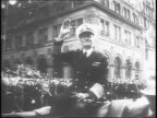 Admiral Chester Nimitz waving to civilians watching the parade / side view of Nimitz's parade vehicle and police escorts / camerman filming the...