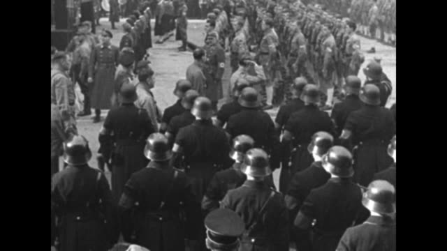 VS Adolf Hitler and Nazi entourage walk through the Odeonsplatz past German soldiers in formation and Hitler Youth in formation during celebration of...