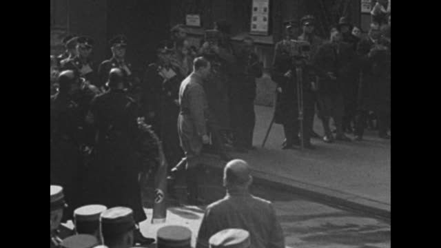 Adolf Hitler followed by Rudolf Hess and others strides past saluting German military officers during commemoration of the 11th anniversary of his...