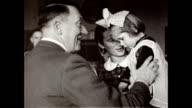 Adolf Hitler greets various women of his domestic staff / woman carrying a young girl wearing bow in her hair approaches Hitler / Hitler shake hands...