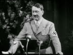HITLER Adolf Hitler in uniform standing behind podium speaking large seated crowd of soldiers Nazi flag waving in wind