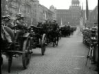 Adolf Hitler riding car down Prague street LA WS Swastika flag on top of building MS German troops parading MS Officials standing WS Tanks down...