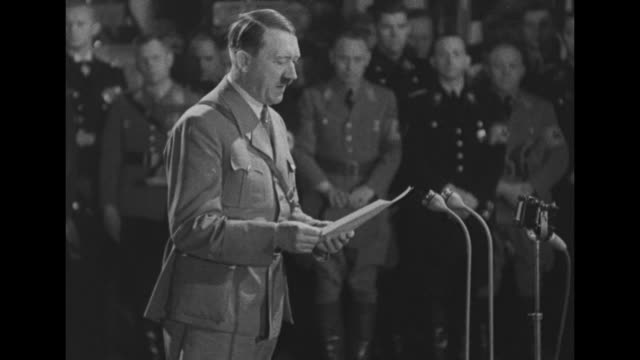 Adolf Hitler walks across stage in room surrounded by members of Nazi party and is handed sheet of paper with election results on it / Hitler...