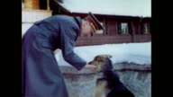 Adolf Hitler with his dog Blondi on the snow covered terrace of Berghof / Blondi running towards Hitler / Hitler petting Blondi / Blondi looking...