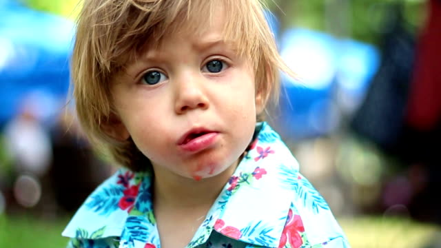 Adorable blue-eyed kid eating a strawberry