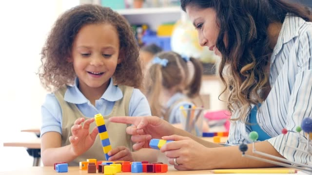 Adorable mixed race kindergarten student counts with counting cubes