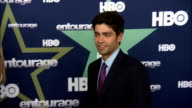 Adrian Grenier moving along the red carpet posing holding up peace sign and saluting paparazzi on the red carpet at the Beacon Theater