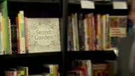 Adult colouring book at top of international bestseller list ENGLAND London INT Drawing books on shelf Reporter to camera People along in bookshop