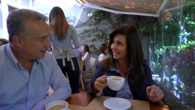 Volwassen paar in een restaurant genieten van een kopje koffie en te praten met een leuke tijd