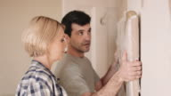 Adult couple fixing painting on the wall