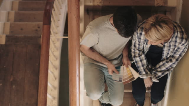 Adult couple looking at colour swatch on staircase in new home