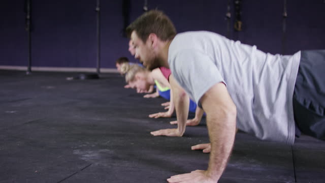 Adult exercise class doing pushups together in gym