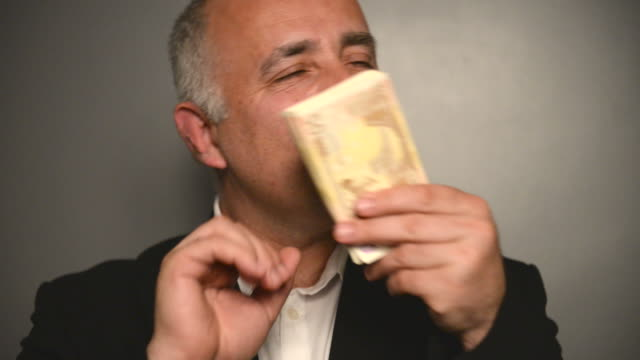 Adult gray-haired man with money on a gray background.