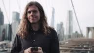 Adult Male with long hair taking selfie on brooklyn bridge