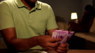 Adult man counting indian two thousand banknotes at home, Delhi, India