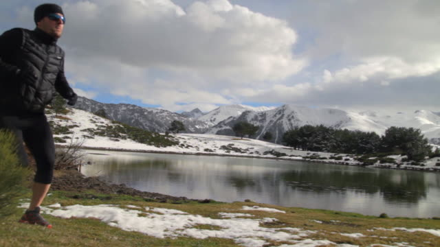Adult man cross country running on the shore of a lake in a snowy mountain range