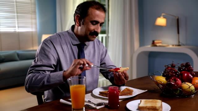 Adult man eating breakfast at home, Delhi, India