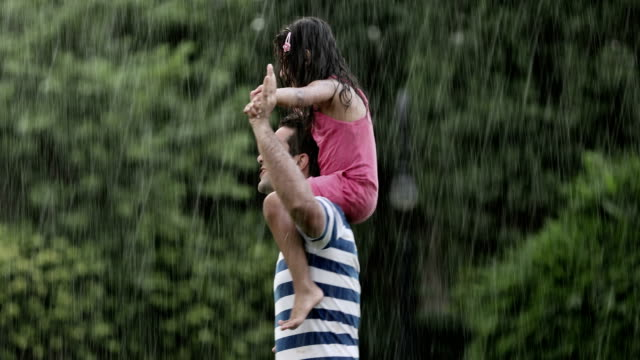 Adult man enjoying in the rain with his daughter, Delhi, India